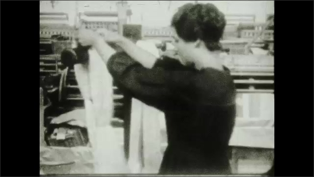 """1930s: Intertitle about raw silk comes to the mill in bales, is unpacked and skeins are straightened for winding on bobbins and fitted on a rack"""". Woman unwinds bobbin."""