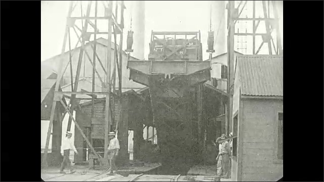 1930s: Industrial lift at factory raises end of shipping trailer, dumping sugar cane onto conveyor belt. Workers watch.