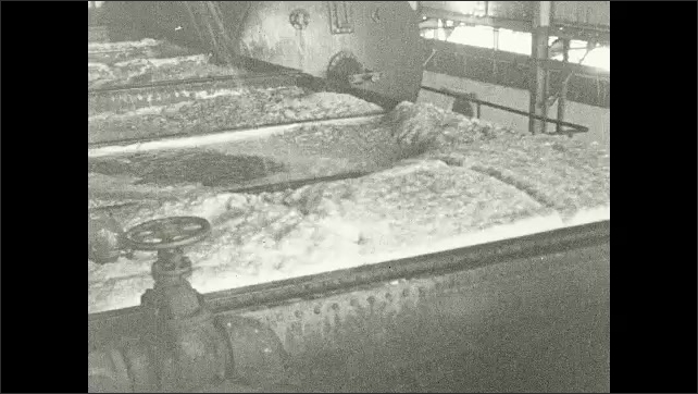 1930s: Vats of molasses bubble inside factory. Title card.