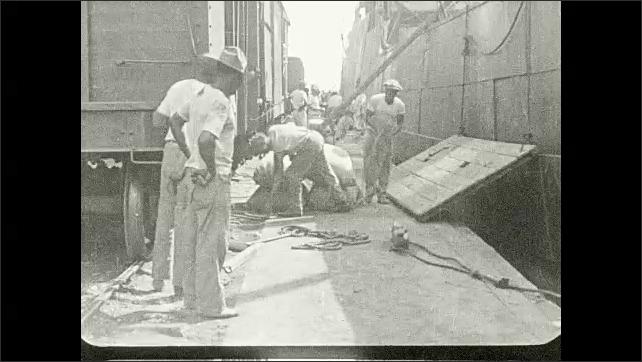 1930s: Men at trainyard unload bags of sugar. Title card.