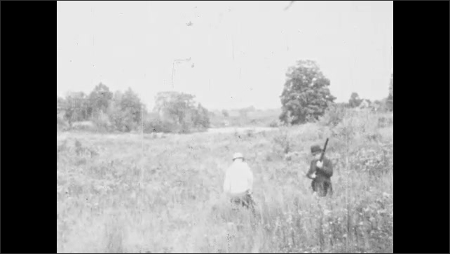 1930s: UNITED STATES: hunters walk through long grass. Dog in long grass. Dog stalks bird