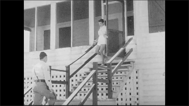1950s: South Carolina Highway Patrol car pulls up to beachside home. Woman exits house and greets highway patrolman. Utility crews load trailer with telephone poles.