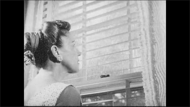 1950s: People secure boats in marina. Woman looks through blinds outside. Wind and rain batter a city street.
