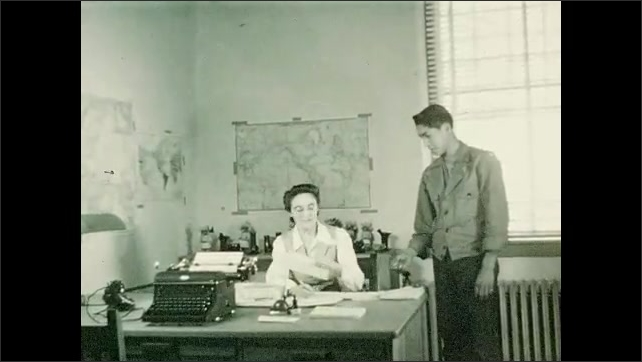 1940s: A woman at a desk hands a man and envelope and he leaves the office. A woman enters and is also handed an envelope. Another man enters and receives an envelope too.