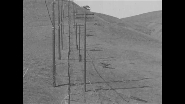 1920s: Men reel old telephone wires onto a spool on the back of a tractor. They remove spool and roll it along the ground.