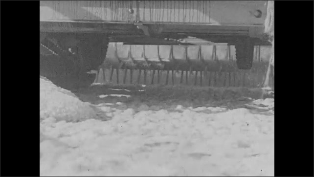 1920s: Machinery operates at a salt company. A screw conveyor moves the salt toward a conveyor belt.