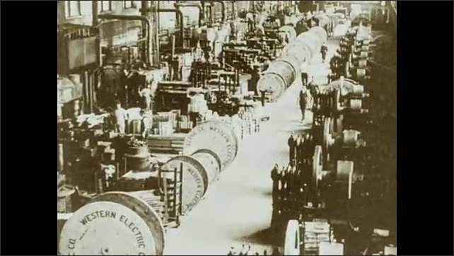 """1930s: Several workers sit and operate machines inside a factory. Big wheels with text """"Western Electric CO"""" rotate inside factory, people walk around big machines."""
