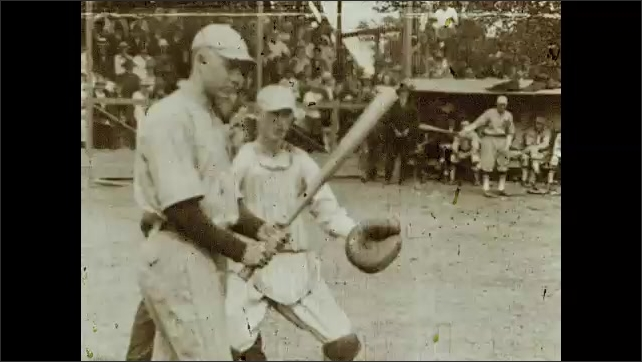 1930s: Children on swings at a playground surrounded by trees. Baseball player prepares to throw ball, player prepares to hit. Men play baseball. Women and children sit at table under trees.