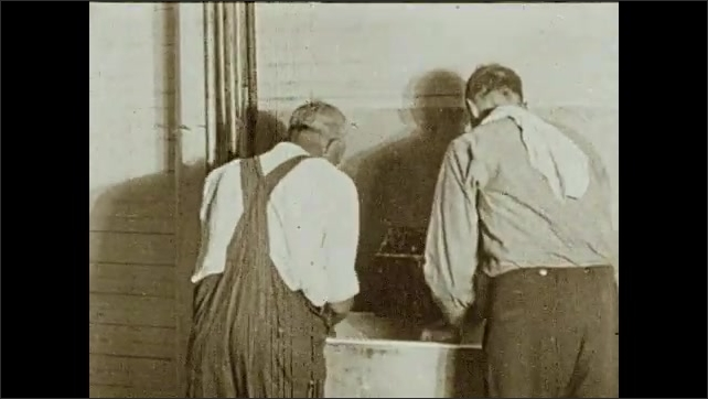 1930s: Men speak next to machines, walk away. Men wash themselves, a man comes and drinks water, two men wash themselves. Man stands and talks to man who sits at desk in an office. Intertitle.