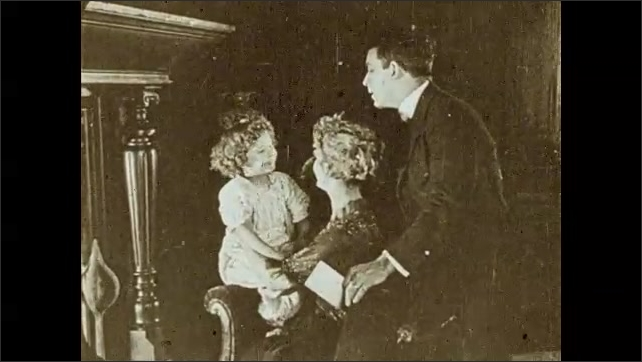 """1930s: Woman and man sit on armchair, smile and talk, child approaches them, woman holds the child and sits her on the armchair, they talk and smile. Intertitle """"The End"""". Film leader with letters."""