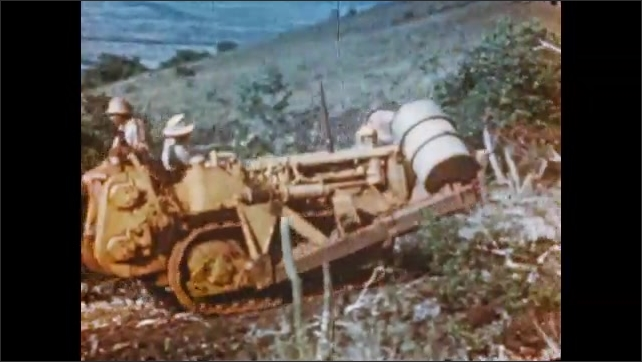 1950s: Man wears a hat and speaks, mountain in background. Cerro Bol??var hill. Man drives tractor that carries barrels. Donkeys carry goods. Two men set a big drill on the top of a mountain.