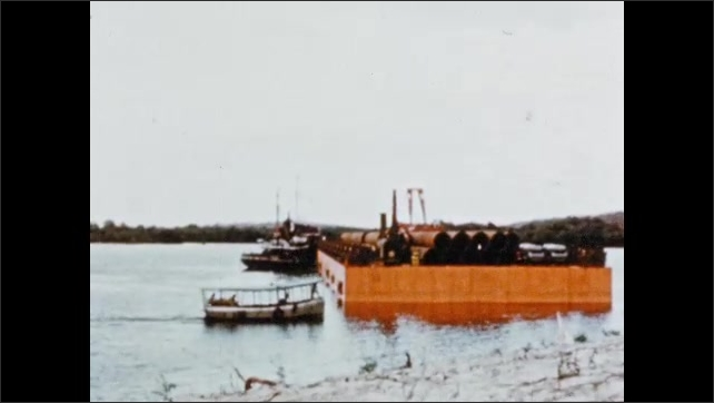 1950s: Boat pulls a large steel barge near the shore. Boat moves in direction of barge. Barge on the shore. Bulldozers push the ground.