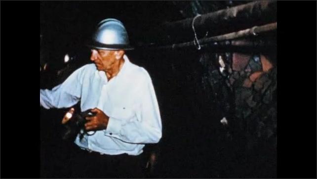 1950s: South America: men visit mine. Men wear hard hats. Board members explore tunnel.