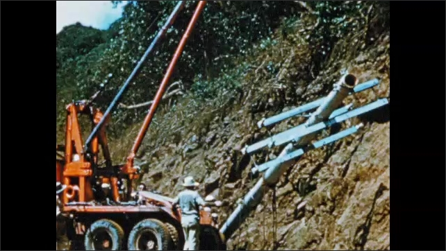 1950s: South America: bulldozer moves soil on slope. Men install pylon pole on slope. Pylons across slope