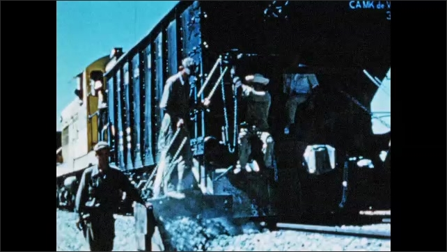 1950s: South America: rock on conveyor belt. Train moves rock along tracks at quarry. Workers spread ballast on floor.