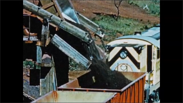1950s: South America: power shovels move soil at mine. Trucks on platform. Ore cars filled from conveyor. Truck unloads ore