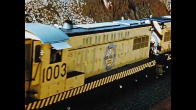 1950s: South America: ore train moves along track. Ore train from above.