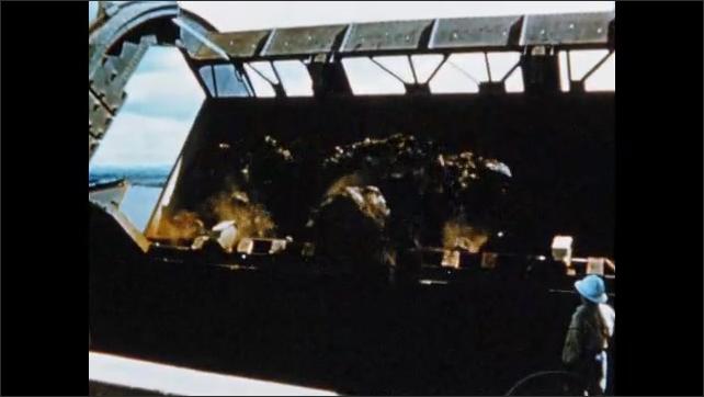 1950s: Train car enters machine.  Rotary railcar dumper empties car.  Man watches.