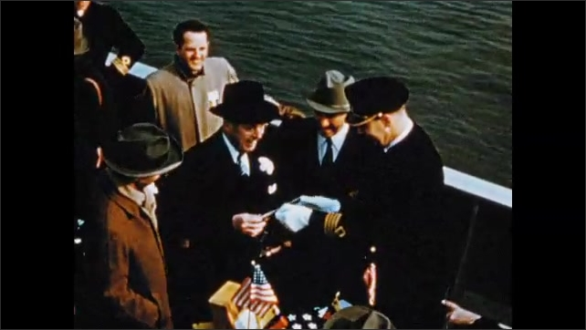 1950s: Man films.  Men pose with gift.  Ship moves down river.