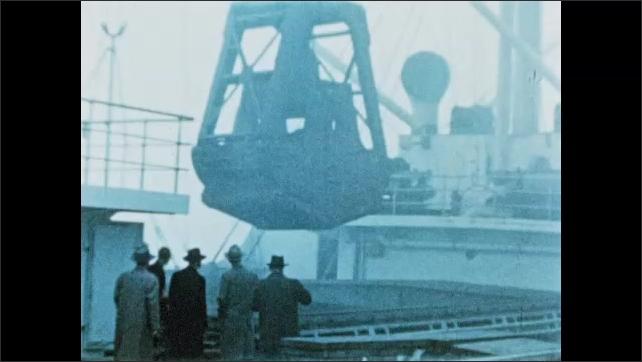 1950s: Crane unloads iron ore from ship.  Men watch.