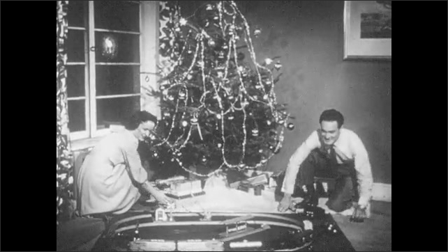 1950s: Father puts toy engine on a track. Father crosses fingers and flips switch. Toy train starts moving on track. Mother and Father sit and watch in delight as toy train goes around track.