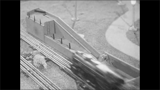1950s: Multiple model trains run on elaborate layout. Model trains pass through tunnels. Adults smile and watch. Signal lights flash. Car automatically unloads lumber on to conveyor belt.