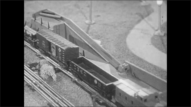 1950s: Model train pulls forward and loads lumber on to car from conveyor belt. Model milk car pulls up to platform.