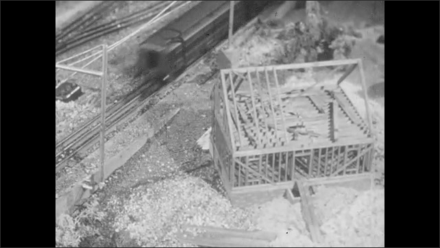 1950s: Barriers go down at a model railway crossing and a crossing watchman pops out of signal box as a train goes by. Coal car butts up to a coal unloader. Coal car unloads into hopper.