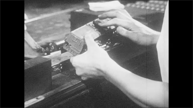 1950s: Factory workers hand assemble model railroad cars and test model railway set elements.