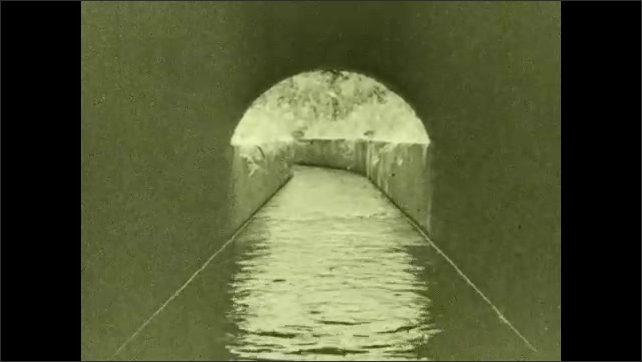 1930s: Water flows through canal, under tunnel. Intertitle card. Wheels on electric pump spin.