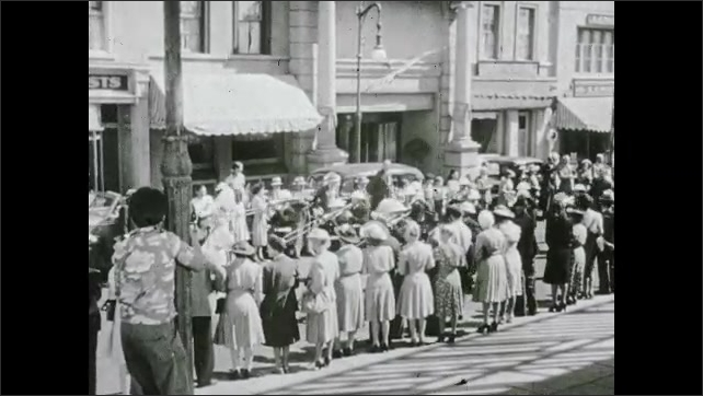 1940s: Men and women crowd streets of neighborhood and watch parade. Soldiers play instruments in marching band on city street.