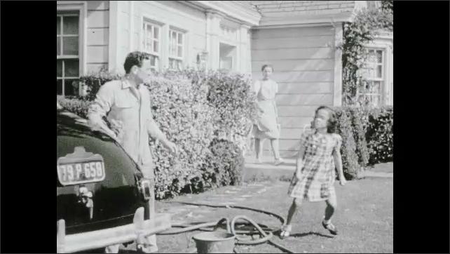 1940s: Battleships explode at docks. Girl runs to man washing car. Girl runs across street and speaks to woman. Man stops washing car. Woman stares in concern.