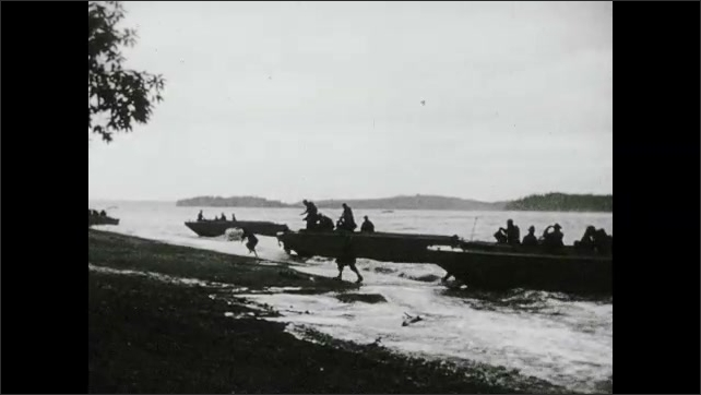 1940s: Soldiers fire howitzers. Ground explodes near jeep. Soldiers disembark rafts and run through shallow ocean onto beaches. Water explodes behind raft.