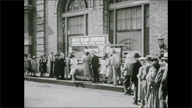 "1940s: People line up, wait outside building, ""Buy war bonds, Help win the war"" sign."