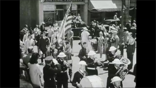 1940s: City street, parade, baton twirler, marching band, man carries American flag, men salute, stand with hats over hearts. Young men carry suitcases, young woman rushes over, kisses cheek.