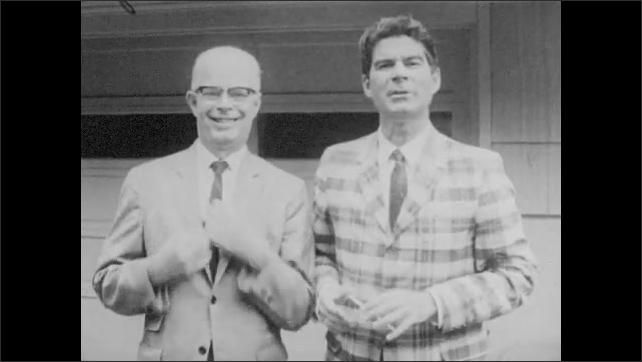 1960s: Men stop in front of garage door. Man with glasses straightens tie. Men smile and speak.