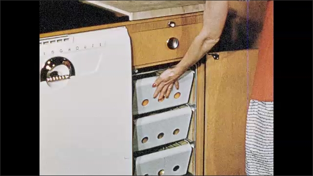 1950s: arm opens drawer to put trash in garbage can with automatic lid. hand grabs door opens to show baskets with potatoes, grabs oranges, puts fruit on cutting board and slices rind with knife.