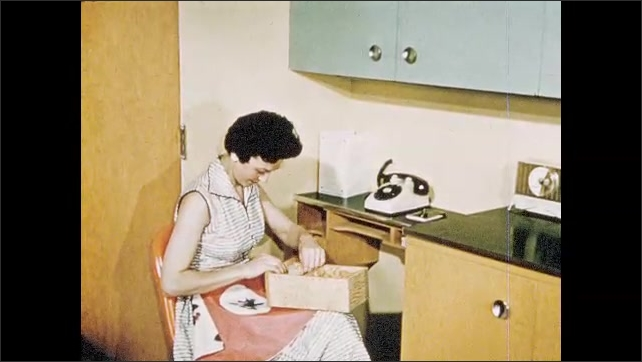 1950s: woman in apron sits at counter, hangs up telephone, pulls out drawer, flips through recipe cards, keeps card and puts wood bin back inside slot in kitchen.