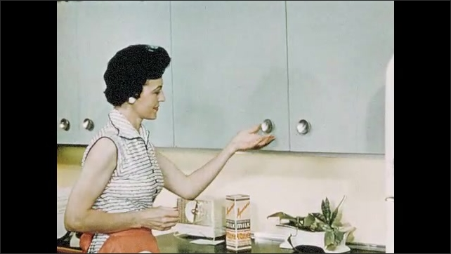 1950s: woman in apron stands, places recipe card on counter, opens door, pulls up shelf with mixer from inside cabinet. Lady opens cabinets to get food. hands pull rolling pin and spoon from drawer.