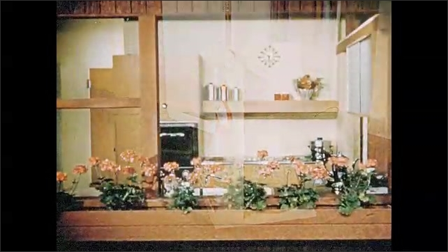 1950s: hands pick up bowl off retractable tray. woman in apron checks pot lid inside cabinet storage space.  vacuum cleaner sits on cart on kitchen floor. flowers grow in window box outside house.