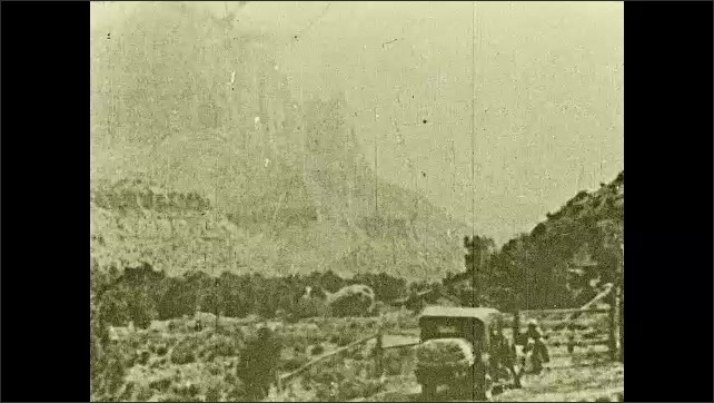 1930s: Intertitle. A woman opens a wooden gate in the desert, a car leaves and stops after the gate, woman closes the gate and enters the car, mountains in the background.