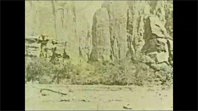 1930s: Intertitle. Two persons walk in the middle of trees, Angel's Landing mountain in background. Cliffs.