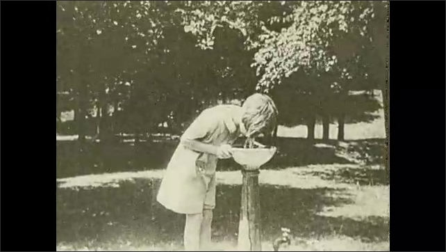 1930s: UNITED STATES: overhead view of people in city street. Girl drinks from water fountain. Boy drinks water from fountain. Rural house and yard. What is lacking here title.