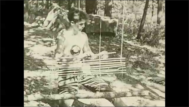 1930s: UNITED STATES: boy weaves wood outdoors. Boys make mattress from wood