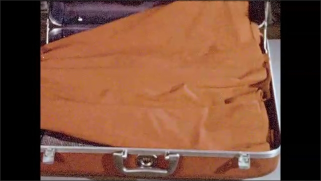 1950s:  lady takes clothes from rail. Lady packs full skirt inside suitcase. Hands fold full skirt inside case.