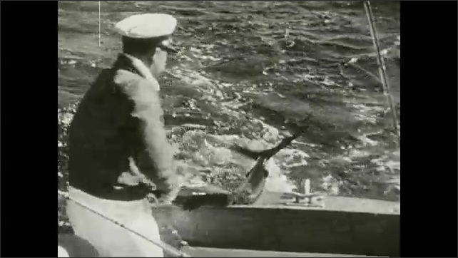 1930s: Swordfish jumps and struggles on fishing line in sea. Hands pull line and operate fishing reel. Men pull swordfish from ocean. Large fish jumps and struggles on fishing line.