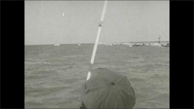 1930s: Man pulls struggling swordfish onboard fishing boat. Fishing boat with sail on ocean. Men catch large fish with rods. Large fish struggle and jump in lake.