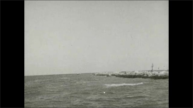 1930s: Men fish from small fishing boat on great lake. Fish struggles on fishing line. Man pulls large fish onboard. Fish jump and fight on fishing lines in lake.