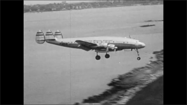1950s: Landing gear of plane lowers. Plane comes in for landing on runway.