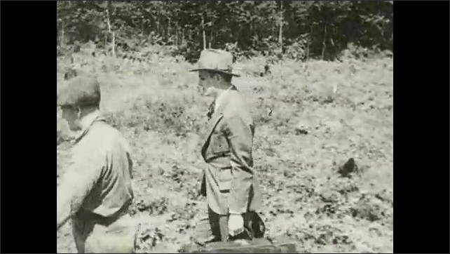 1930s: Man in cap speaks. Men carry luggage and walk along railroad tracks. Men carry luggage and talk.
